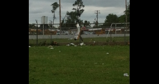 Debris hangs on a fence skirting an athletic field in the central part of the town. (Image: Paul Budd.)