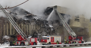 Firefighters in front of the partially destroyed building. (Image: Sergey Leschina.)